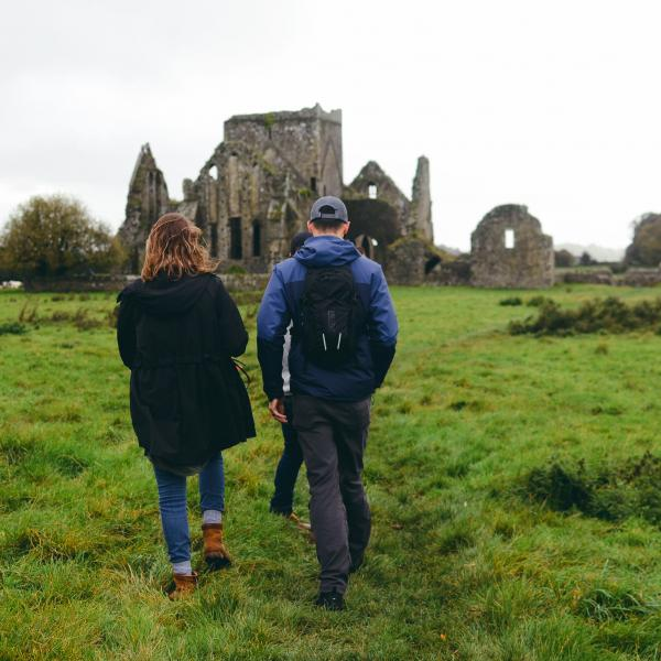 people standing on grass in front of Hore Abbey in Ireland